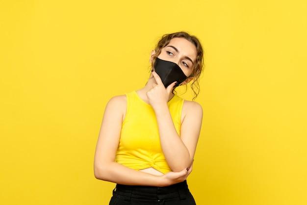Vista frontale della giovane donna che pensa in maschera nera sulla parete gialla