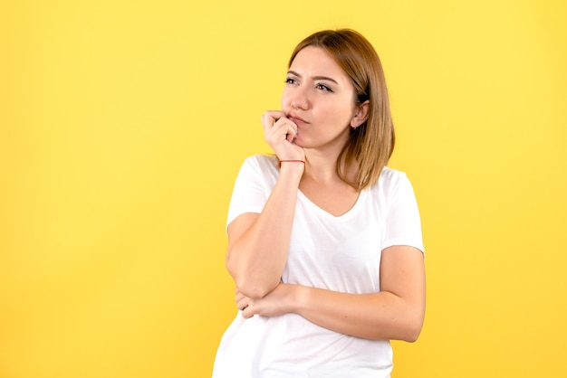 Front view of young woman thinking on yellow wall