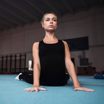 Тренировка молодой женщины перед олимпийскими играми по гимнастике