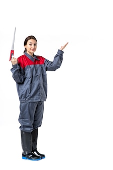 Front view of young woman in uniform holding hacksaw on white wall