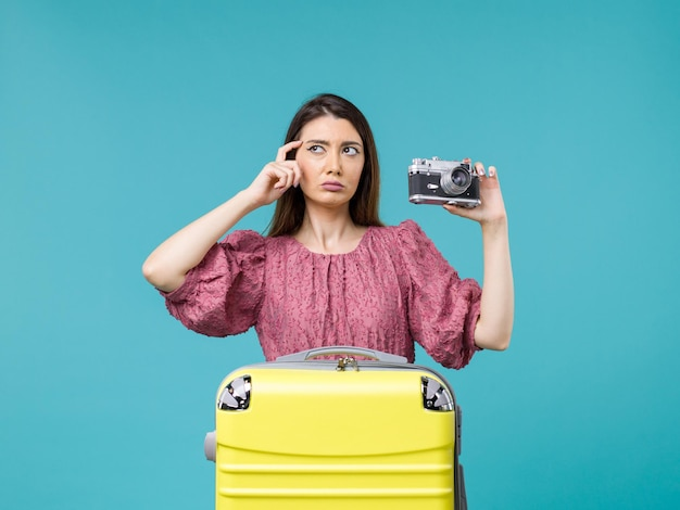 Front view young woman in vacation holding photo camera on blue desk journey sea trip woman abroad vacation