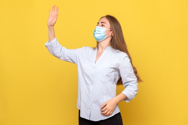 Vista frontale della giovane donna che saluta sulla parete gialla