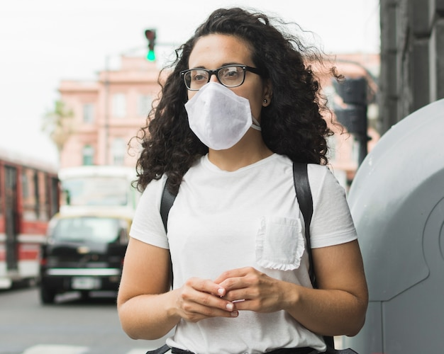 Front view young woman wearing a medical mask outside