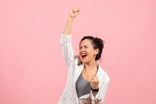 Vista frontale giovane donna che indossa giacca bianca posa emotivamente su sfondo rosa signora moda colore donna emozione woman