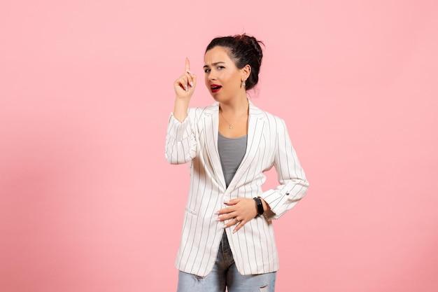 Vista frontale giovane donna che indossa giacca bianca su sfondo rosa donna moda donna emozioni colore