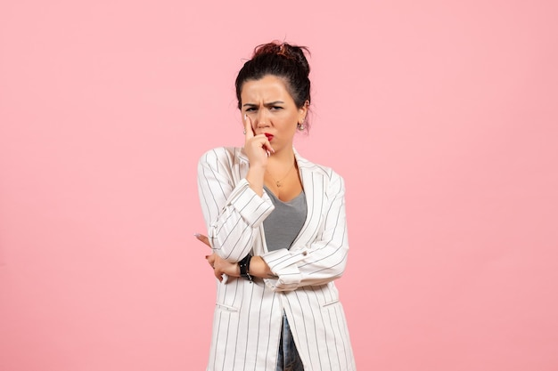 Front view young woman wearing white jacket and posing on pink background lady fashion color woman emotion