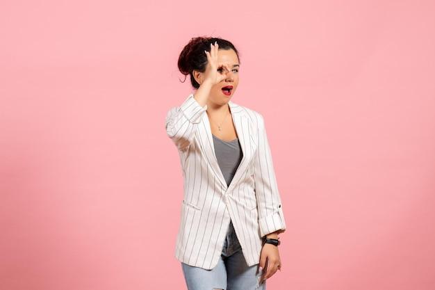Vista frontale giovane donna che indossa giacca bianca in posa su sfondo rosa signora moda donna emozione colore