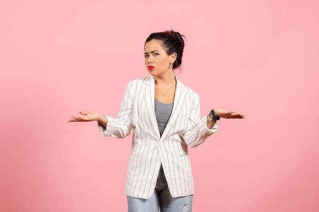 Vista frontale giovane donna che indossa giacca bianca e posa con espressione confusa su sfondo rosa donna moda donna emozioni colore