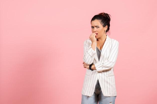 Vista frontale giovane donna che indossa giacca bianca con faccia nervosa su sfondo rosa signora moda donna emozione colore
