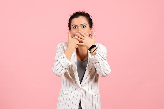 Vista frontale giovane donna che indossa una giacca bianca con la faccia scioccata su sfondo rosa signora moda colore donna emozione Foto Gratuite