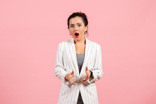 Vista frontale giovane donna che indossa giacca bianca con faccia sorpresa su sfondo rosa donna moda donna emozione colore