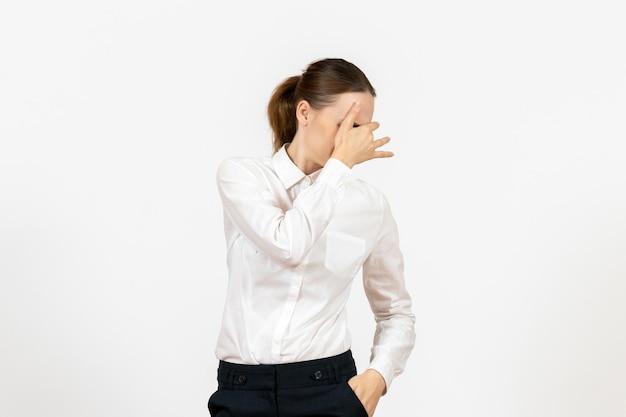 Vista frontale giovane donna in camicetta bianca che copre il viso su sfondo bianco lavoro ufficio emozione femminile modello sentimento