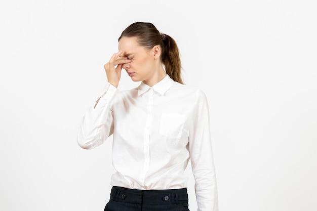 Vista frontale giovane donna in camicetta bianca che ha mal di testa su sfondo bianco lavoro sensazione femminile modello emozione ufficio