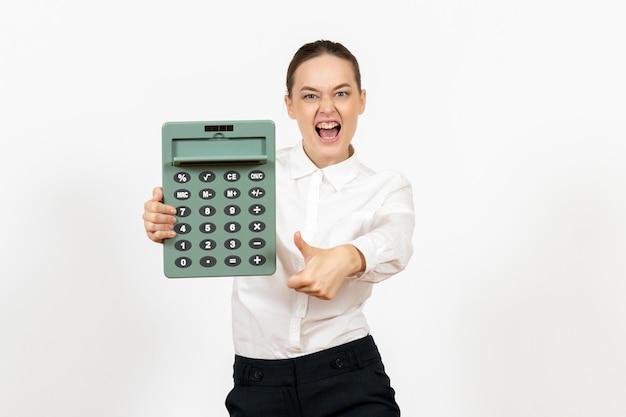 Vista frontale giovane donna in camicetta bianca che tiene grande calcolatrice e urla su sfondo bianco lavoratrice dell'ufficio emozione sensazione di lavoro bianco