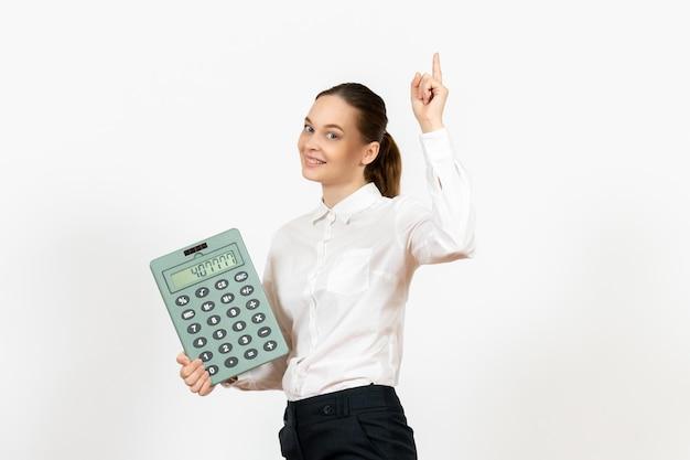 Vista frontale giovane donna in camicetta bianca che tiene grande calcolatrice su sfondo bianco ufficio emozioni femminili sentimenti lavoro lavoratore bianco