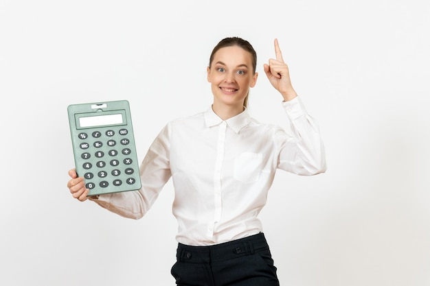 Front view young woman in white blouse holding big calculator on a white background office female worker emotion feeling job white