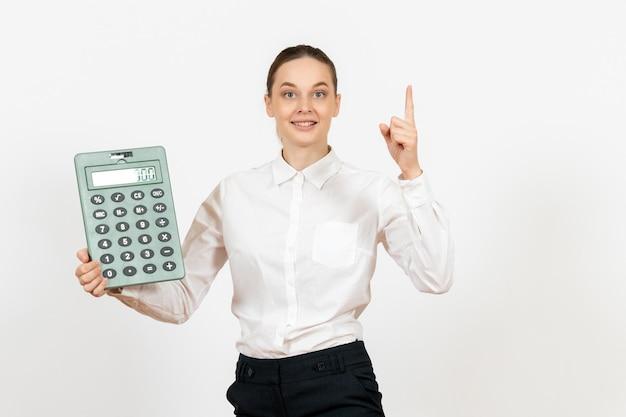 Vista frontale giovane donna in camicetta bianca che tiene grande calcolatrice su sfondo bianco lavoratrice dell'ufficio emozione sensazione di lavoro bianco