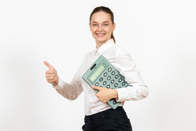 Vista frontale giovane donna in camicetta bianca che tiene grande calcolatrice su sfondo bianco lavoratore emozione femminile lavoro d'ufficio bianco