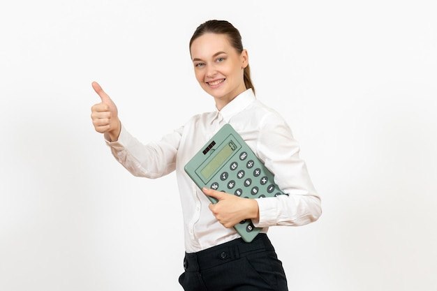 Front view young woman in white blouse holding big calculator on the white background worker female emotion office job white