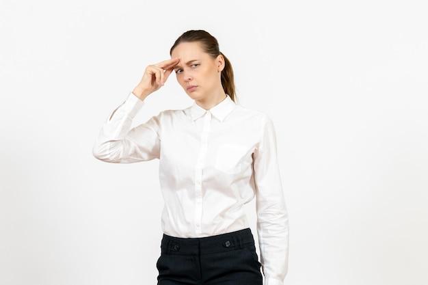 Vista frontale giovane donna in camicetta bianca pensando su sfondo bianco lavoro d'ufficio emozione femminile modello di sentimento feeling
