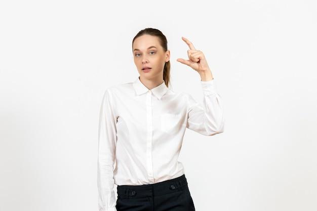 Vista frontale giovane donna in camicetta bianca con espressione annoiata su sfondo bianco lavoro ufficio femminile sentimento modello emozione