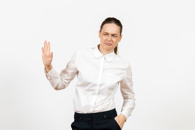 Vista frontale giovane donna in camicetta bianca con faccia confusa su sfondo bianco lavoro ufficio emozione femminile modello di sentimento