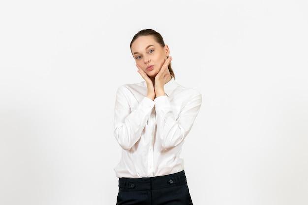 Vista frontale giovane donna in camicetta bianca con faccia da civetta su sfondo bianco lavoro ufficio sensazione femminile modello emozione