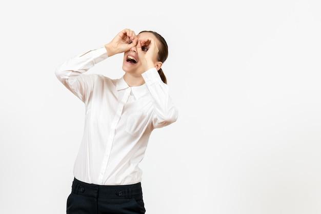 Vista frontale giovane donna in camicetta bianca con la faccia eccitata su sfondo bianco lavoro ufficio femminile sentimento modello emozione