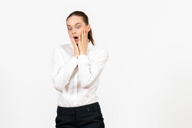 Vista frontale giovane donna in camicetta bianca con faccia scioccata su sfondo bianco lavoro d'ufficio modello di sentimento femminile emozione Foto Gratuite