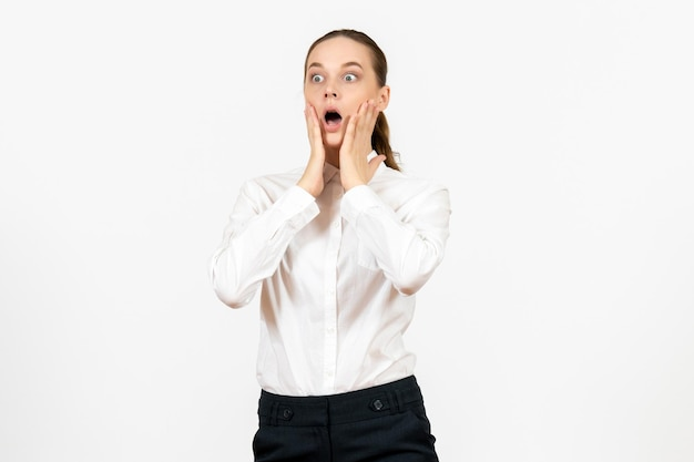 Vista frontale giovane donna in camicetta bianca con faccia scioccata su sfondo bianco lavoro d'ufficio emozioni femminili sensazione modello