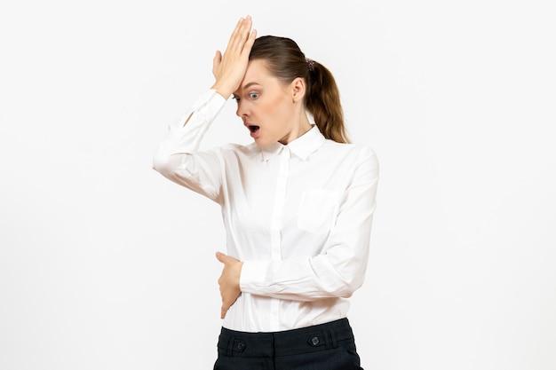 Vista frontale giovane donna in camicetta bianca con la faccia scioccata su sfondo bianco lavoro d'ufficio emozioni femminili modello di sentimenti