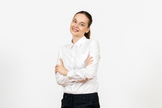Vista frontale giovane donna in camicetta bianca con volto sorridente su sfondo bianco lavoro femminile sentimento modello ufficio emozioni