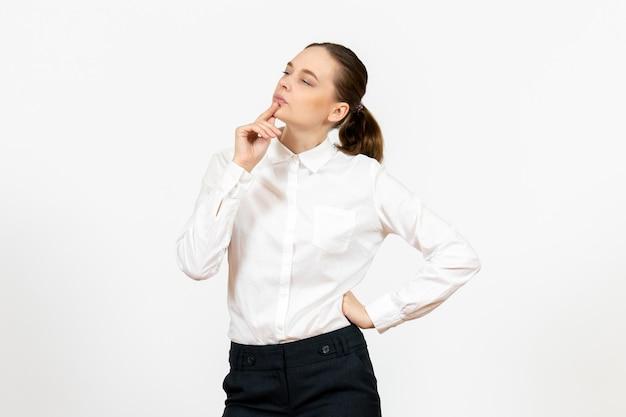 Vista frontale giovane donna in camicetta bianca con espressione pensante su sfondo bianco lavoro d'ufficio modello di sentimento femminile emozione