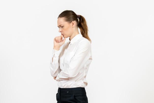 Vista frontale giovane donna in camicetta bianca con faccia pensante su sfondo bianco ufficio emozione femminile sentimento modello lavoro model