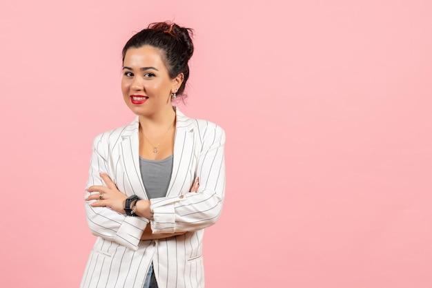 Vista frontale giovane donna in giacca bianca in posa su uno sfondo rosa signora moda colore donna emozione Foto Gratuite