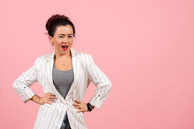 Vista frontale giovane donna in giacca bianca in posa con faccia curiosa su sfondo rosa signora moda colore donna emozione