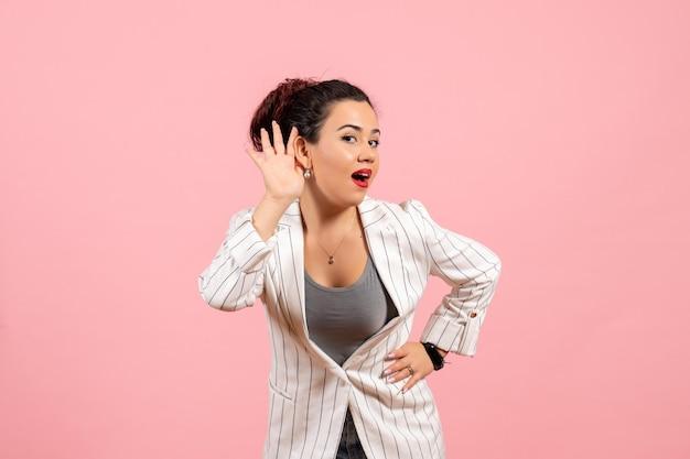 Vista frontale giovane donna in giacca bianca che cerca di ascoltare su sfondo rosa signora moda colore donna emozione