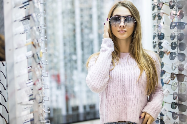 Front view of young woman in white sweater try glasses in professional store on