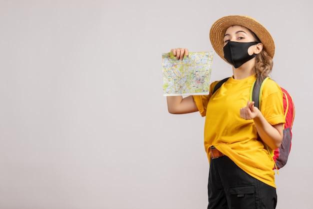 Giovane donna di vista frontale con lo zaino che sostiene la mappa che fa il segno dei soldi