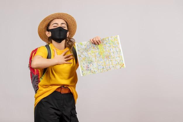 Giovane donna di vista frontale con lo zaino che sostiene la mappa che mette la mano sul suo petto