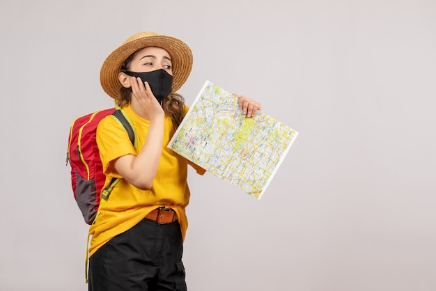 Front view young woman with backpack holding up map
