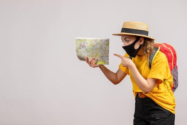 Giovane donna di vista frontale con lo zaino che indica alla mappa