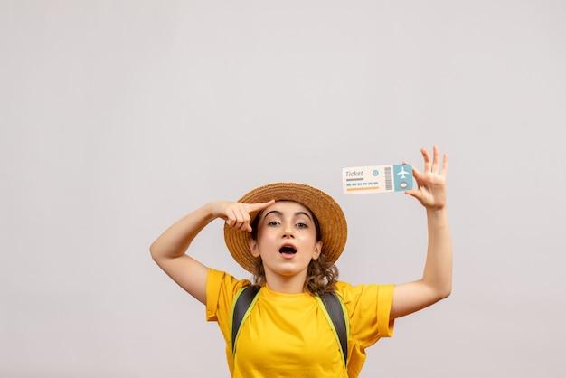 Giovane donna di vista frontale con lo zaino che indica al biglietto di viaggio