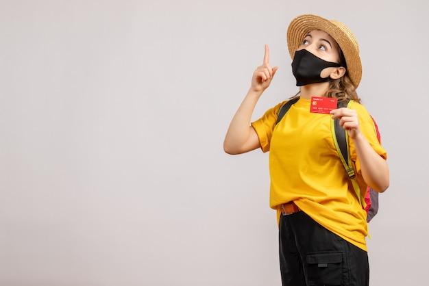 카드를 가리키는 손가락을 들고 검은 마스크와 전면보기 젊은 여자