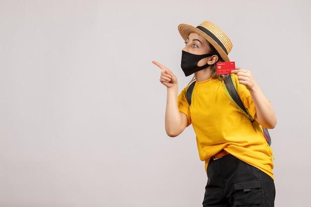 왼쪽 손가락으로 가리키는 카드를 들고 검은 마스크와 전면보기 젊은 여자