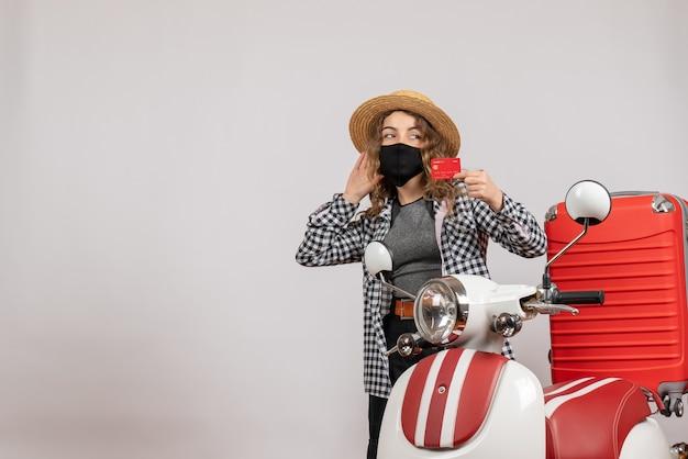 Vista frontale giovane donna con maschera nera che tiene la carta in piedi vicino al motorino rosso