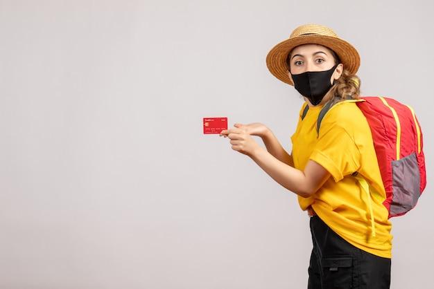 카드를 들고 검은 마스크와 전면보기 젊은 여자