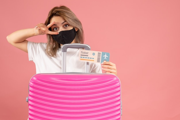 Front view young woman with black mask holding ticket standing behind pink suitcase