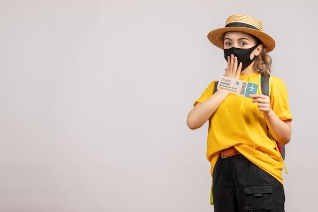 Молодая женщина с черной маской, держащая проездной билет, вид спереди