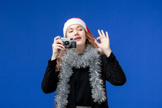 Vista frontale della giovane donna con la macchina fotografica sulla parete blu